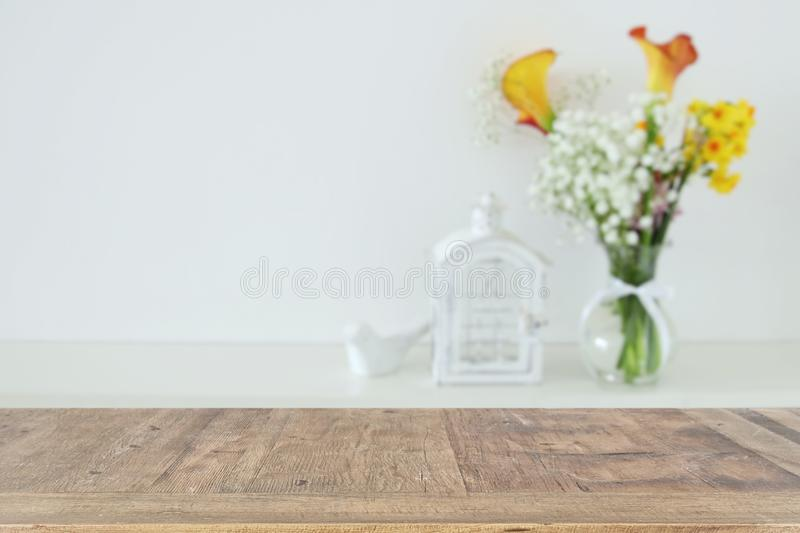 Beautiful flowers in the vase in front of wooden empty table. Ready for product display presentation. Beautiful flowers in the vase in front of wooden empty royalty free stock photography