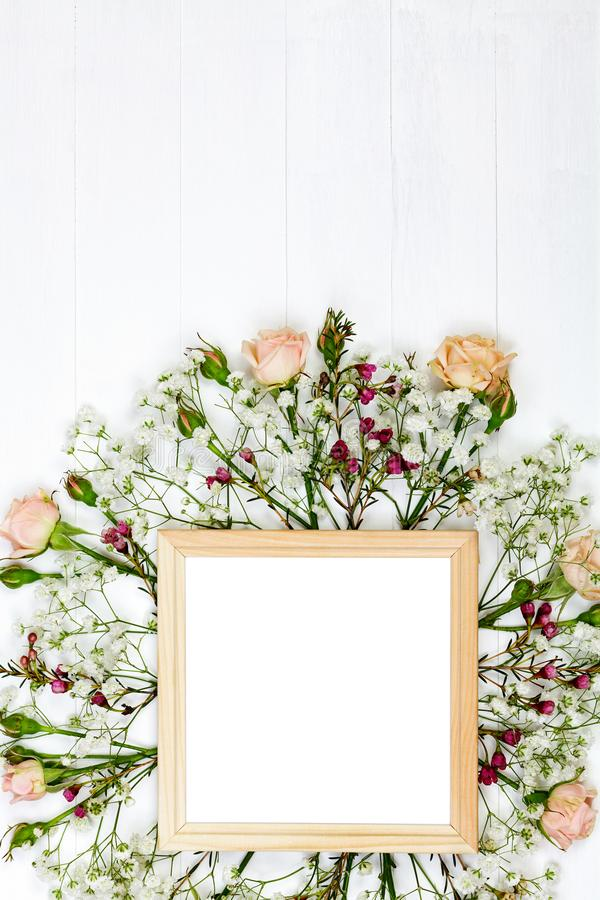 Beautiful flowers and wooden photo frame on white wooden table. Beautiful flowers and wooden photo frame on white table. Flat lay style royalty free stock image