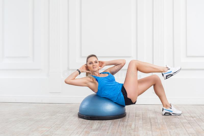 Beautiful focused sporty young athletic blonde woman in black shorts and blue top working in gym doing exercises for abdominal. Muscles on bosu balance trainer royalty free stock image