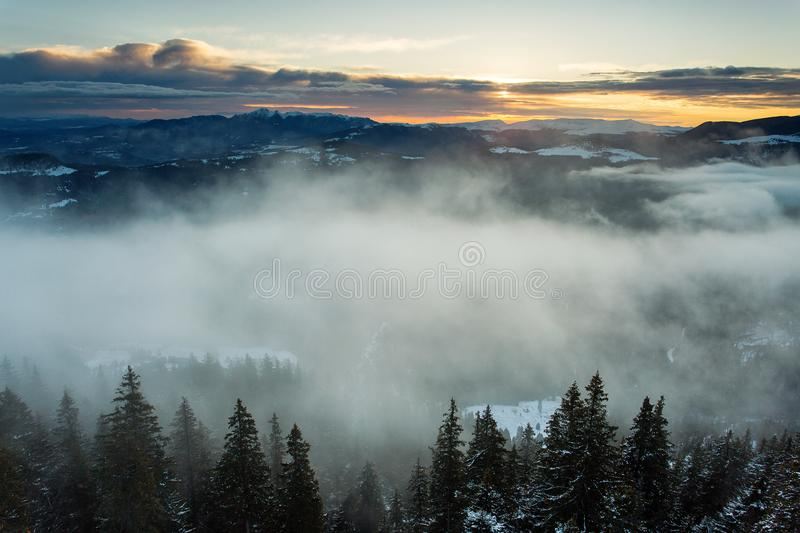 Beautiful fog over forest in mountin with sunrise in background stock image