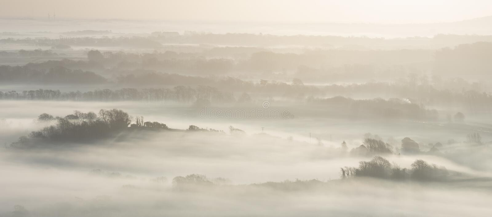 Stunning foggy English rural landscape at sunrise in Winter with. Beautiful foggy English countryside landscape at sunrise in Winter with layers rolling through royalty free stock images