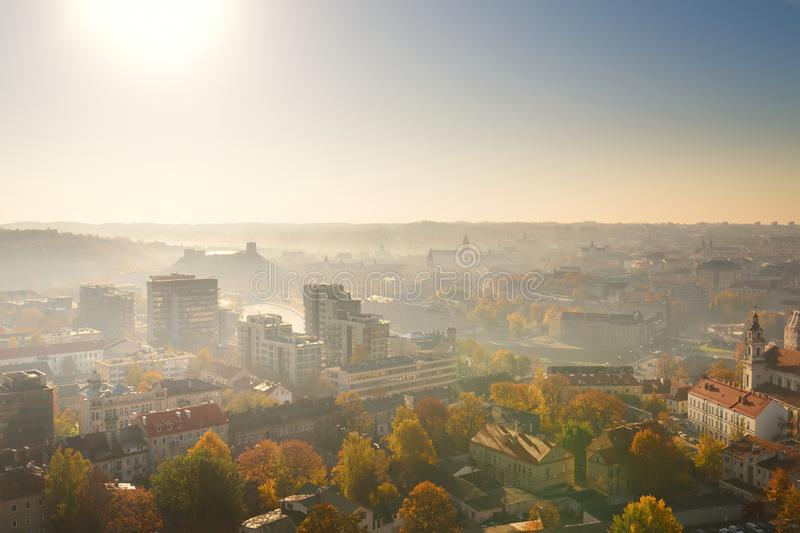 Beautiful foggy Vilnius city scene in autumn with orange and yellow foliage. Aerial early morning view stock image