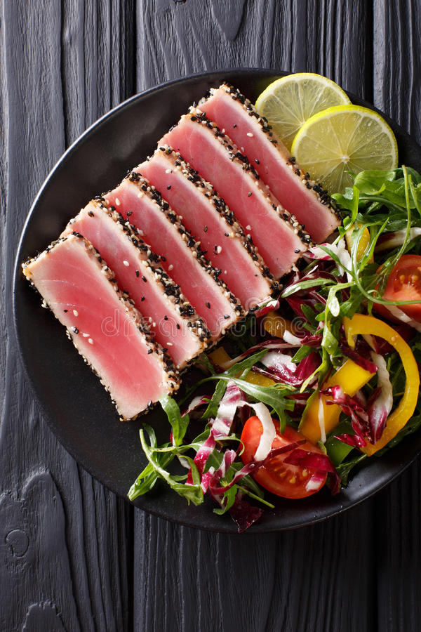 Beautiful food: steak tuna in sesame, lime and fresh salad close. Up on a plate on the table. Top view from above vertical royalty free stock image