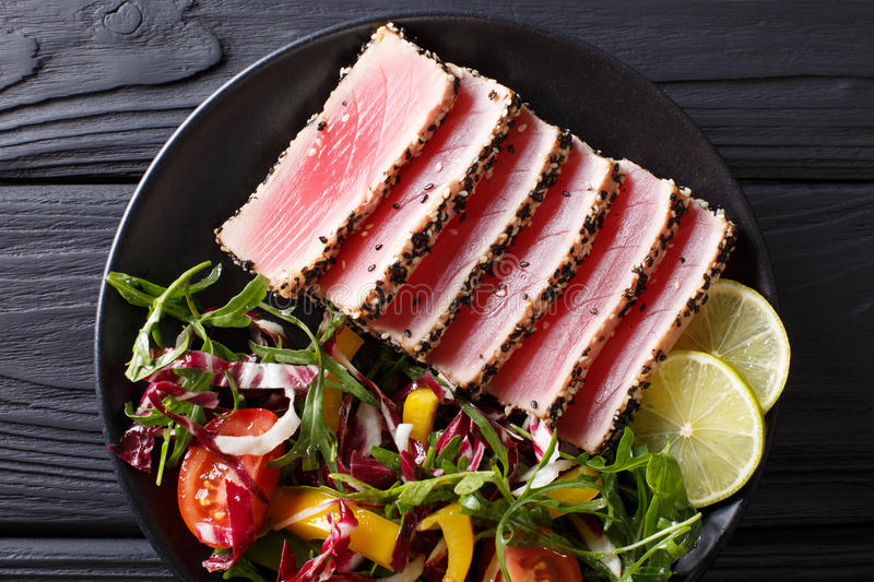 Beautiful food: steak tuna in sesame, lime and fresh salad close. Up on a plate on the table. Top view from above horizontal royalty free stock photos