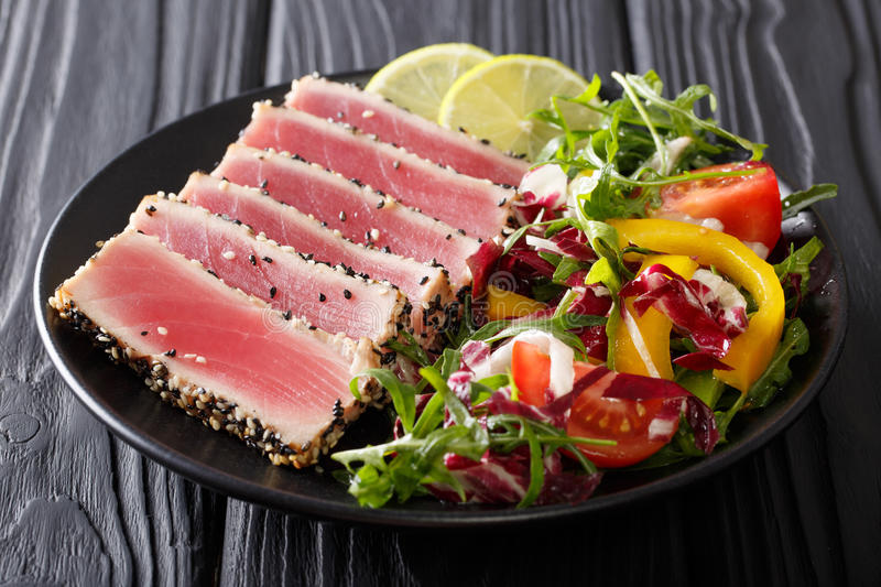 Beautiful food: steak tuna in sesame, lime and fresh salad close. Up on a plate on the table. horizontal stock images