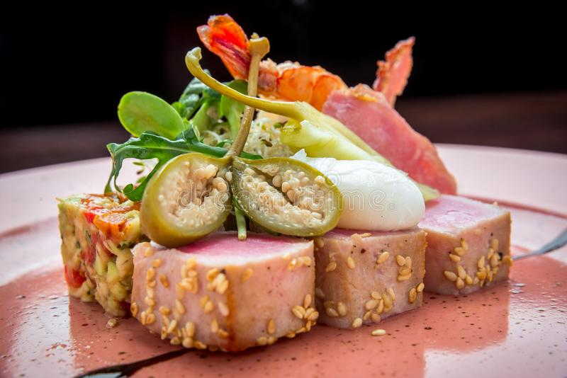 Beautiful food: steak tuna in sesame, lime and fresh salad close-up on a plate. On the table stock photo