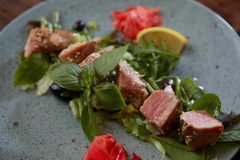 Beautiful food: steak tuna in sesame, lime and fresh salad close-up on a plate on the table. Horizontal stock photography