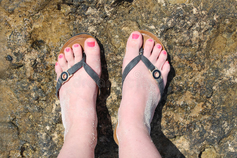 Beautiful foots of young woman wearing in flip flops, top view. Travel stock photo