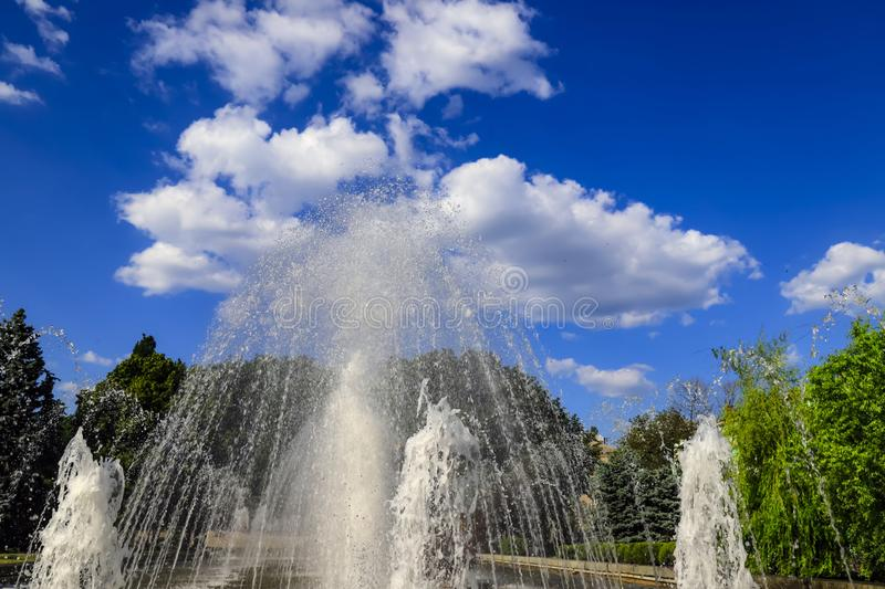 Beautiful fountain against beautiful clouds, spring, summer cityscape, Dnepropetrovsk, Dnepr city, Ukraine. Beautiful fountain against the backdrop of beautiful stock photos