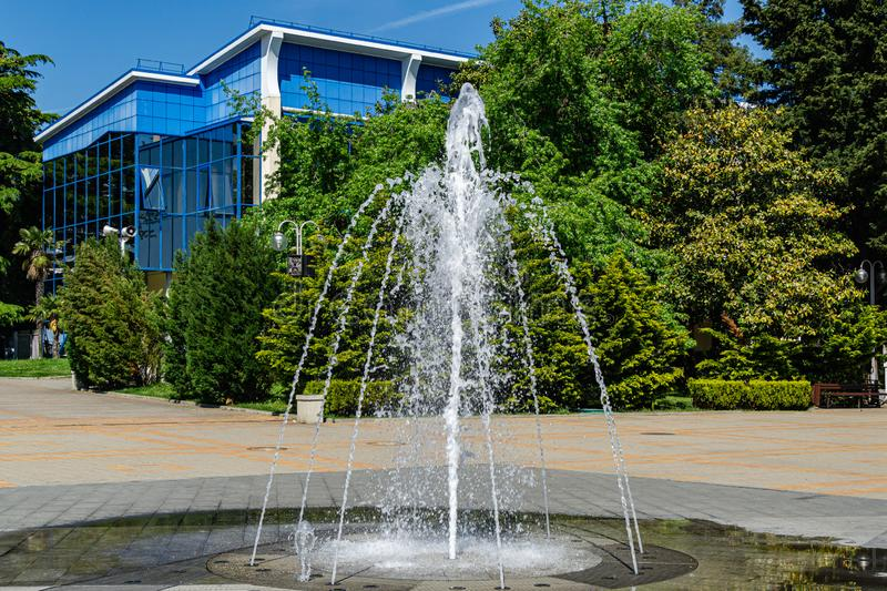 Beautiful fountain on pedestrian-only street on square of October Revolution. On evergreen plants background, and modern building with blue glasses walls in royalty free stock image