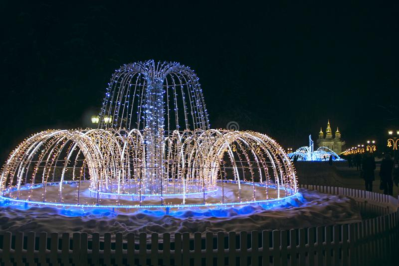 Beautiful fountains in city park. Colorful New Year garlands royalty free stock image