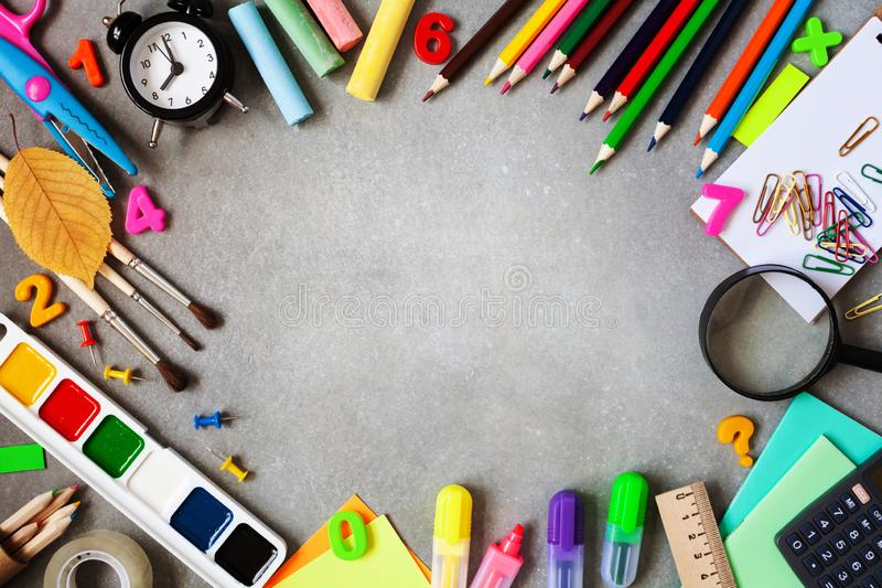 Beautiful frame of different stationery, alarm clock and colorful supplies on gray background. Back to school concept. Top view stock images