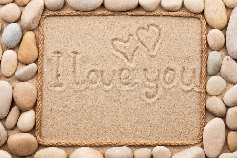 Beautiful frame made of rope and sea shells on the sand with te. Xt i love you, as background stock images