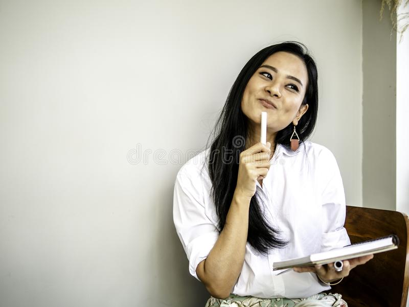 Beautiful freelancer holding a pen and note book in hand, have a lot of creative thinking idea ready to writing or drawing royalty free stock photo
