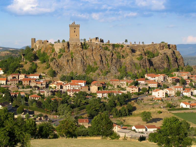 Beautiful french fortification above a town. The town of Puy-en-Velay in France seen in late evening light: the fortress on the hill top and houses at bottom stock photography