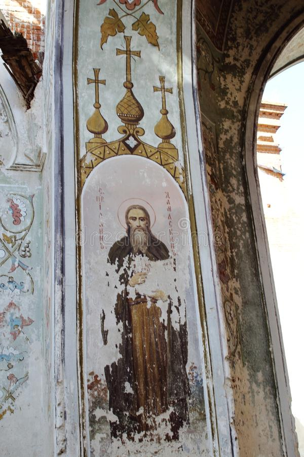 Beautiful fresco St. John of Damascus on wall of destroyed Christian Orthodox Church of St. Nicholas Wonderworker. Concept of royalty free stock images