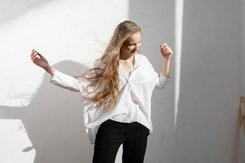 Beautiful fresh blonde model in white shirt and black trousers. stock image