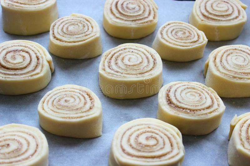 Beautiful fresh cinnamon rolls.Close up. Beautiful fresh cinnamon rolls. The cooking process. Fresh fragrant pastries. Raw dough for buns.Close up royalty free stock images