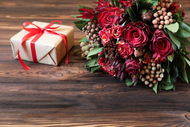 Beautiful fresh flower arrangement of red roses and gift box. stock image