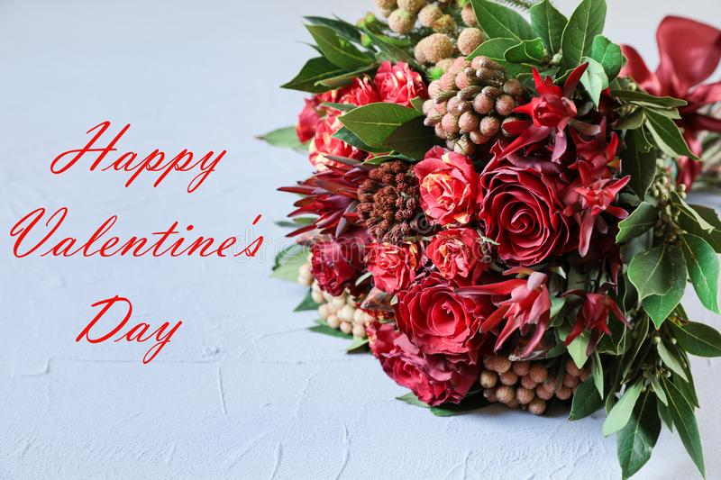 Beautiful fresh flower arrangement of red roses and text wish, Valentines day greeting card concept. stock photography