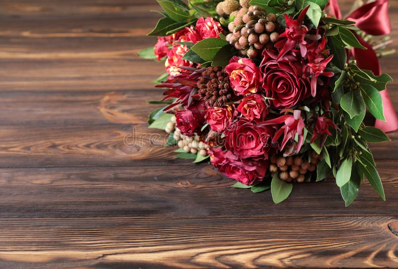 Beautiful fresh flower arrangement of red roses on the wooden background. stock image