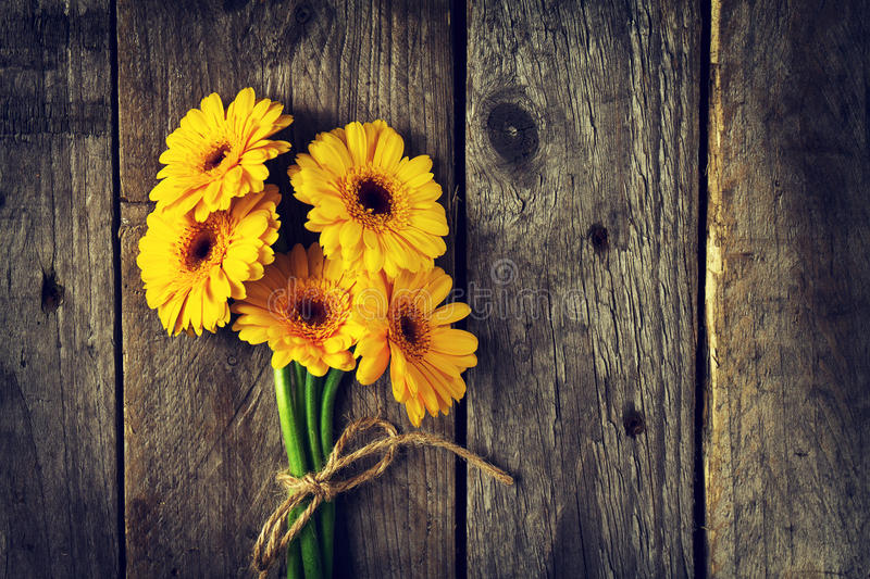 Beautiful Fresh Spring Yellow Bunch of Gerbers on Old Vintage Wooden Table. stock photos
