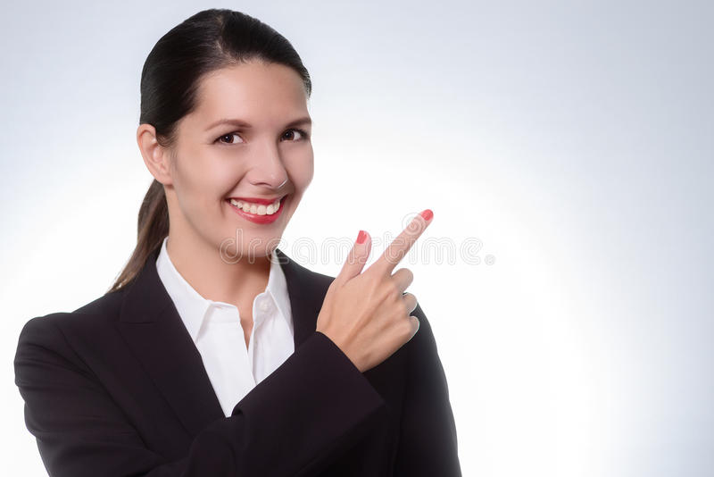 Beautiful friendly manageress pointing to copy space. Beautiful stylish manageress pointing to copy space with a beaming friendly smile as she draws your royalty free stock photos
