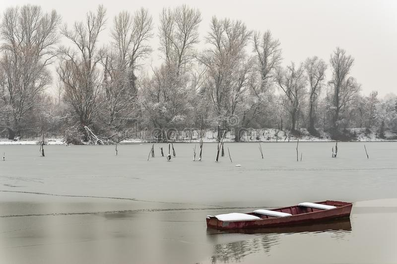 Beautiful frozen river. A boats covered with snow.  stock photography