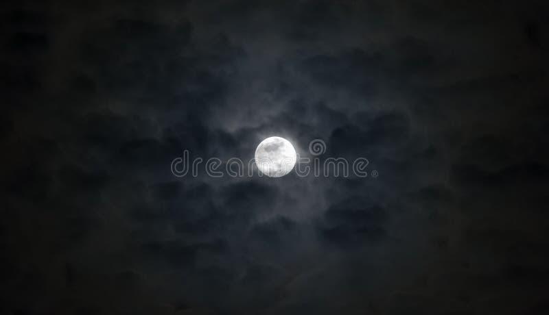 Beautiful full moon beneath wispy blue gray moody clouds, dramatic night sky stock photo