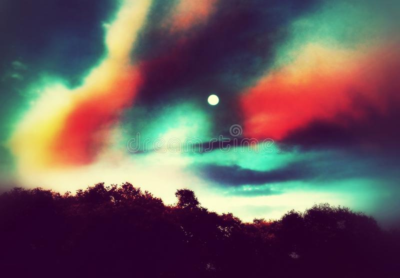 A beautiful full moon in a colorful sky. An illustrative image of a beautiful full moon in a colorful sky over the trees royalty free illustration