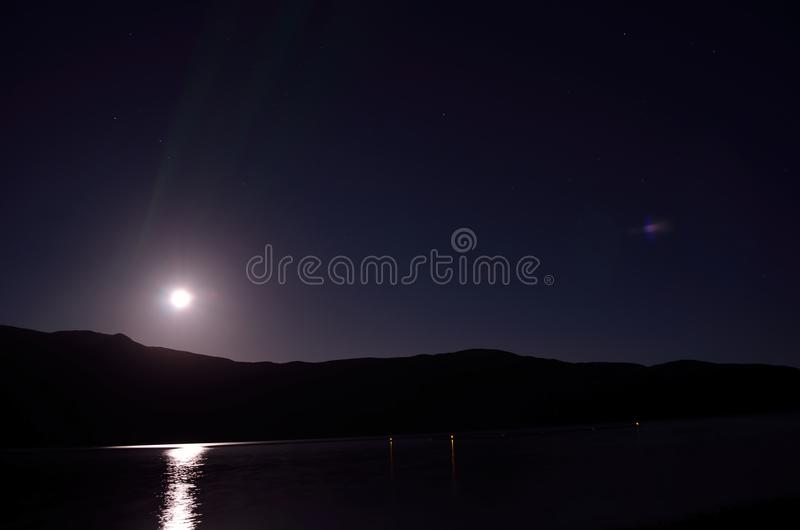 Beautiful full moon over mountain in autumn night. With reflection on fjord surface stock images