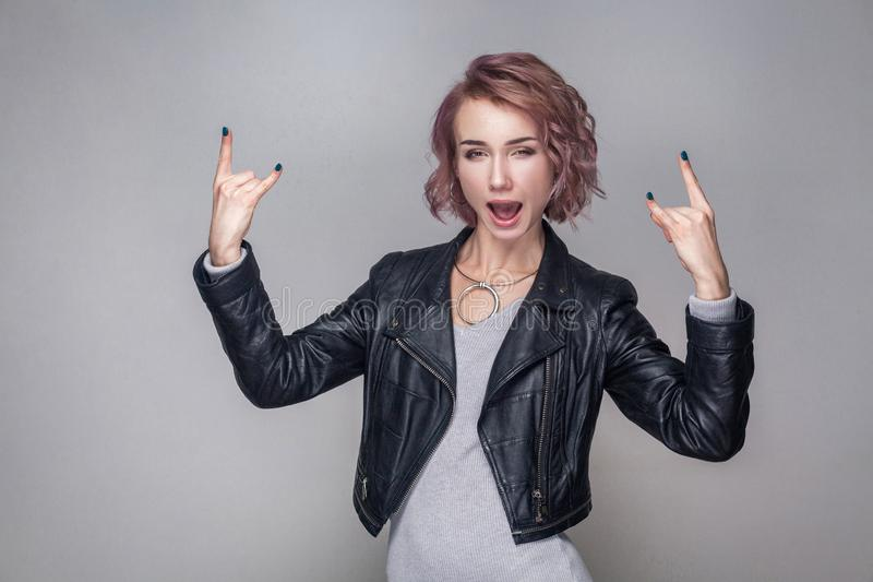 Beautiful funny amazed rocker girl with short hairstyle and makeup in casual style black leather jacket standing with rock sign. And looking at camera. indoor stock photos