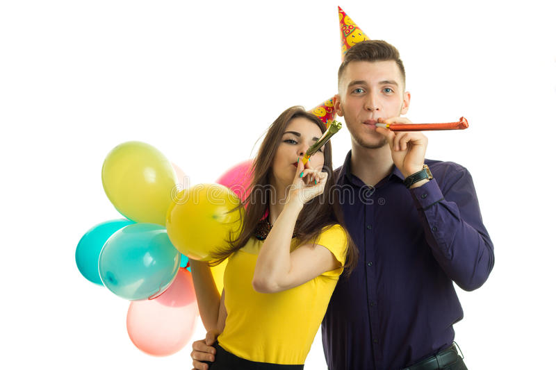 Beautiful and funny girl with boyfriend celebrate birthday hold balls and blow horns stock photo