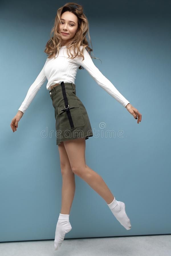 Beautiful funny girl jumping in white t-shirt green skirt and white socks on blue background. Funny and positive royalty free stock photo