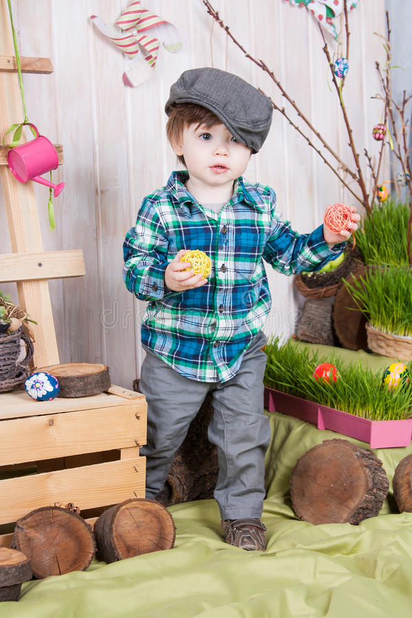 Beautiful funny little boy playing among easter spring scenery. Studio filming a child in a bright, juicy spring location. Child is happy and cheerful stock photos
