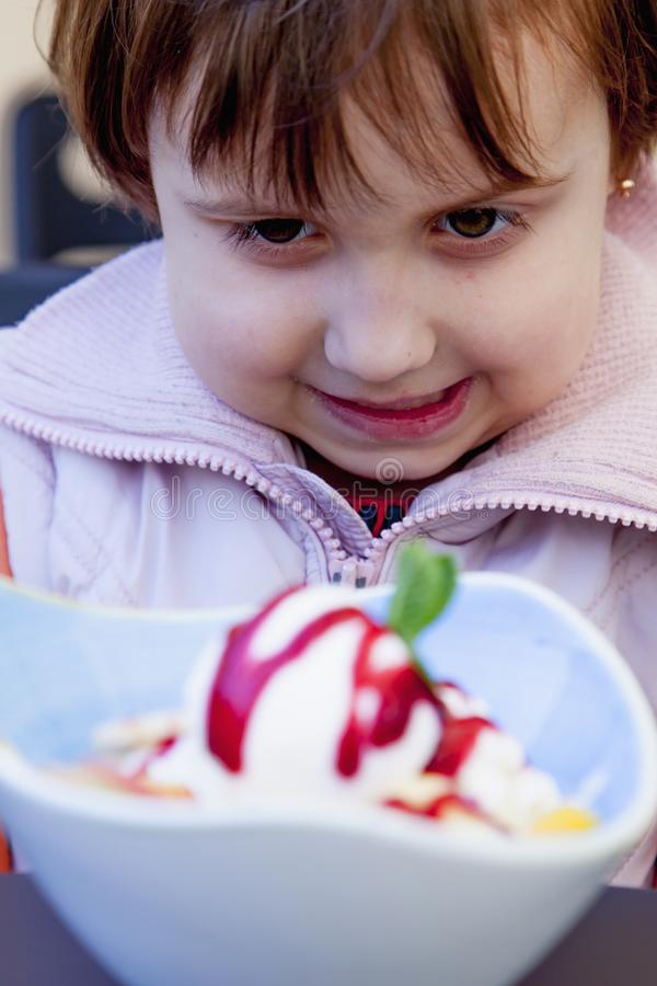 Beautiful little child girl eating ice cream in the summer royalty free stock image