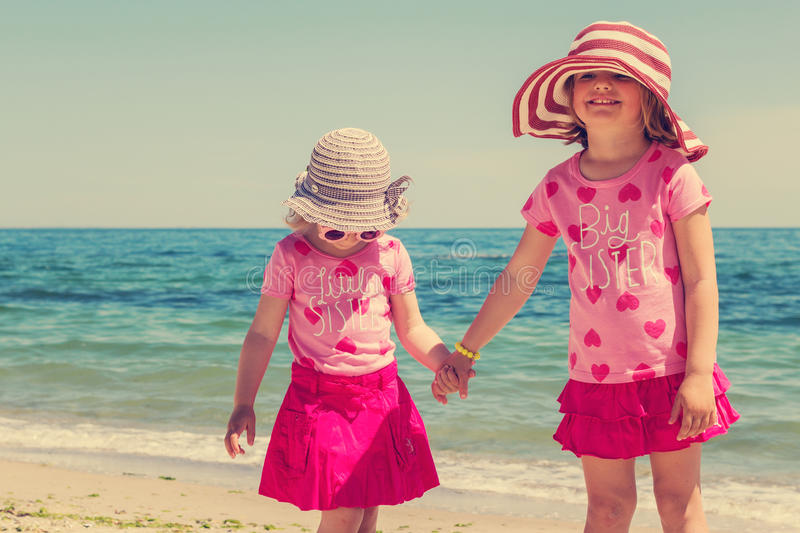 Beautiful funny little girls in striped hats on the beach. stock image