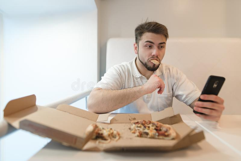 A beautiful and funny man eats a pizza out of the box and picks up his phone. Selfies with pizza stock images