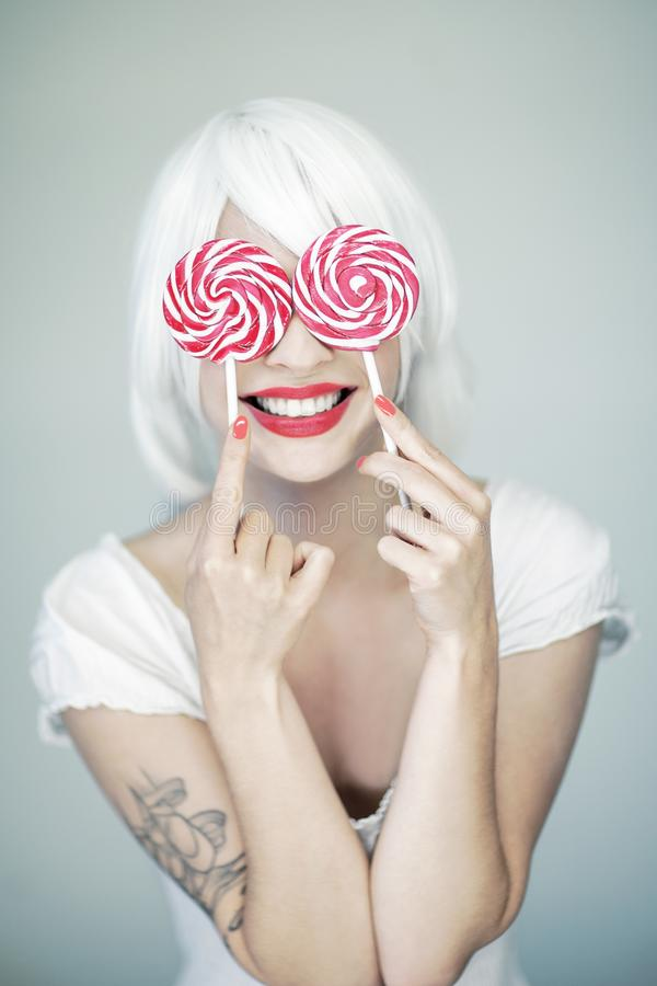 Beautiful funny woman in white and perfect pink makeup holding two swirl lollipops royalty free stock photography