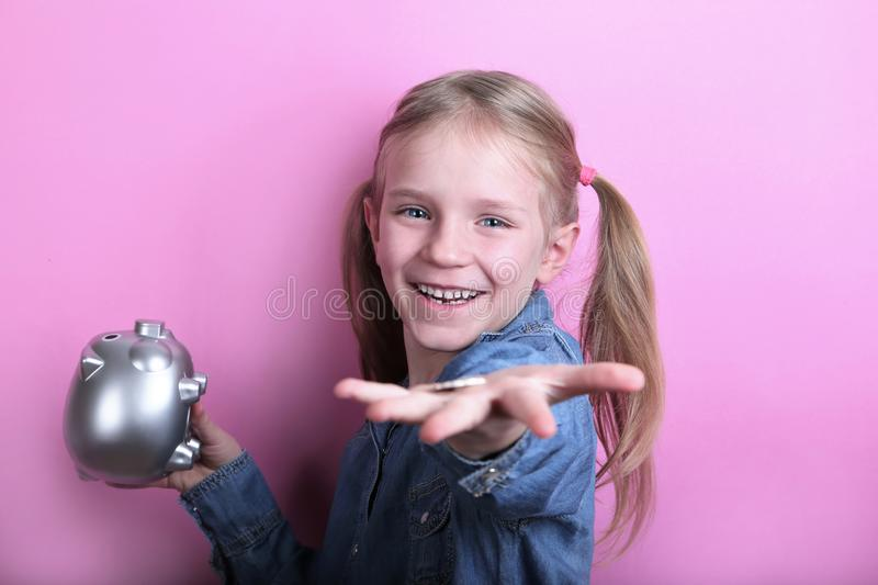 Beautiful funny young girl with silver piggy bank on pink background. save money concept. stock images