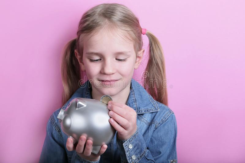 Beautiful funny young girl with silver piggy bank on pink background. save money concept. stock photography