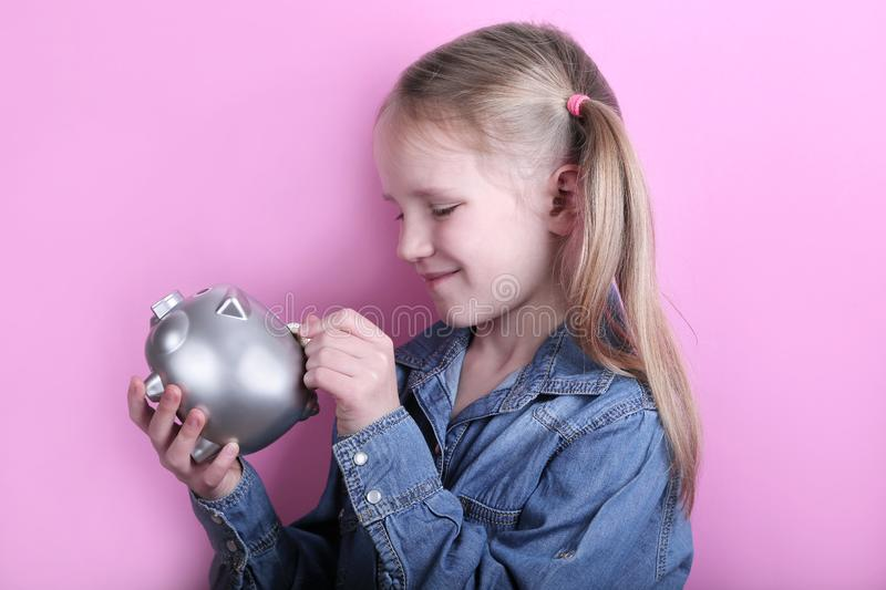 Beautiful funny young girl with silver piggy bank on pink background. save money concept. royalty free stock images