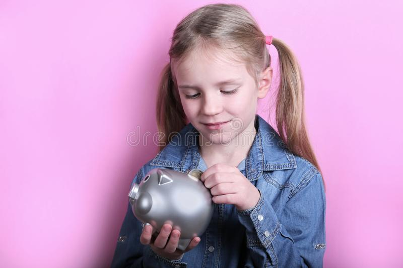 Beautiful funny young girl with silver piggy bank on pink background. save money concept. royalty free stock photography