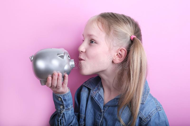 Beautiful funny young girl with silver piggy bank on pink background. save money concept. royalty free stock photos