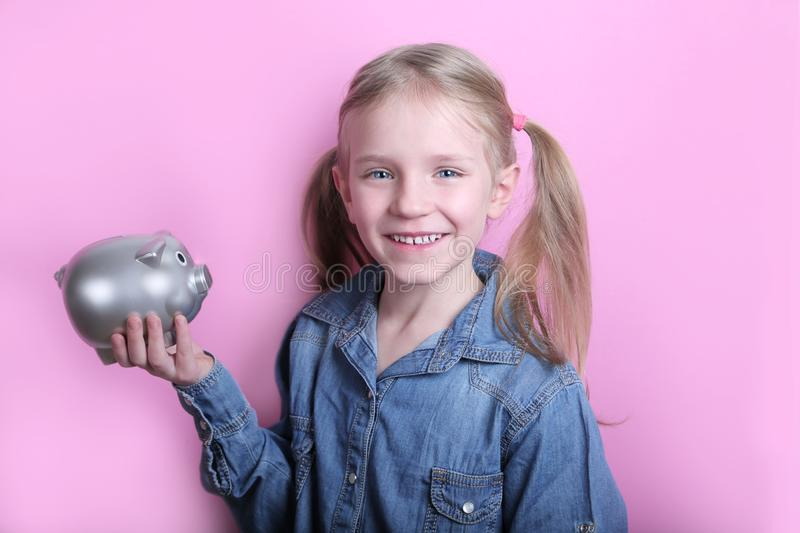 Beautiful funny young girl with silver piggy bank on pink background. save money concept. stock photos