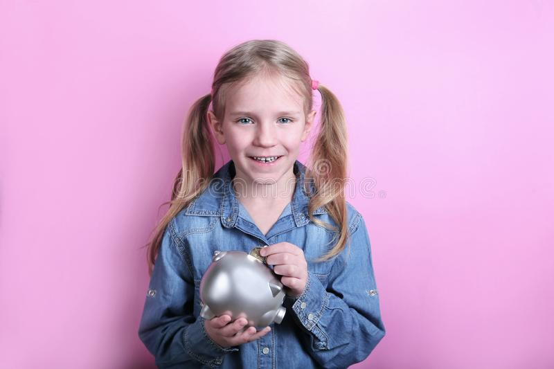 Beautiful funny young girl with silver piggy bank on pink background. save money concept. royalty free stock image