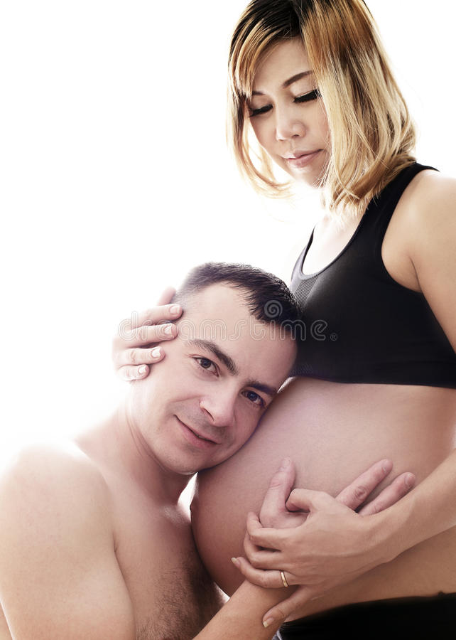 Beautiful future parents: his pregnant asian wife and a happy husband with new life stock photos