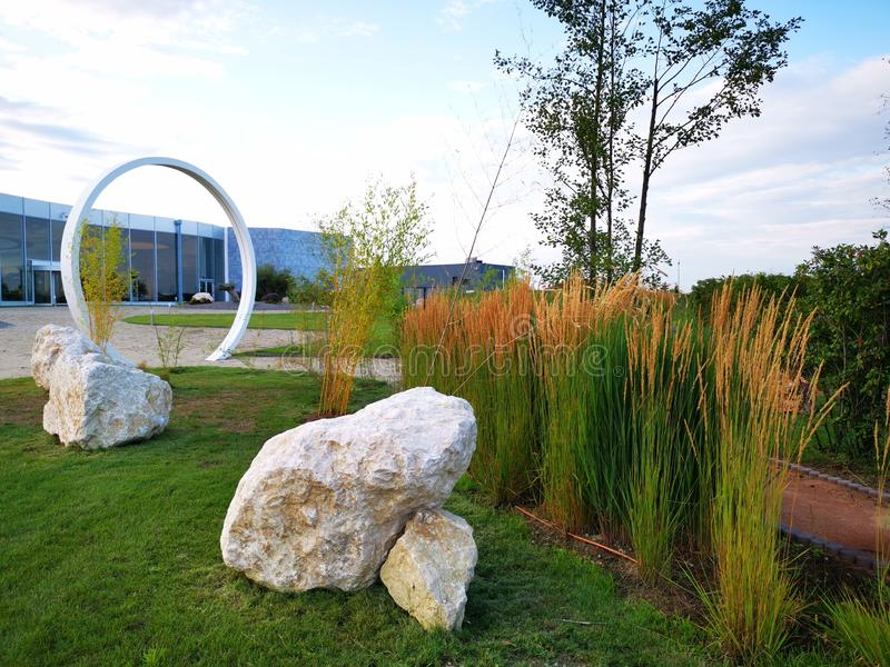 Beautiful garden at Therme Bucharest resort. Beautiful garden at Therme Bucharest, Romania resort.nDecorative stones and reed near round gate. n royalty free stock image