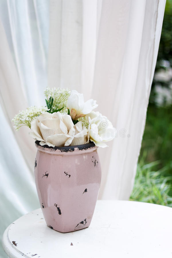 Beautiful garden vase with white roses and other flowers on the table, exterior, gazebo decor idea. stock photography