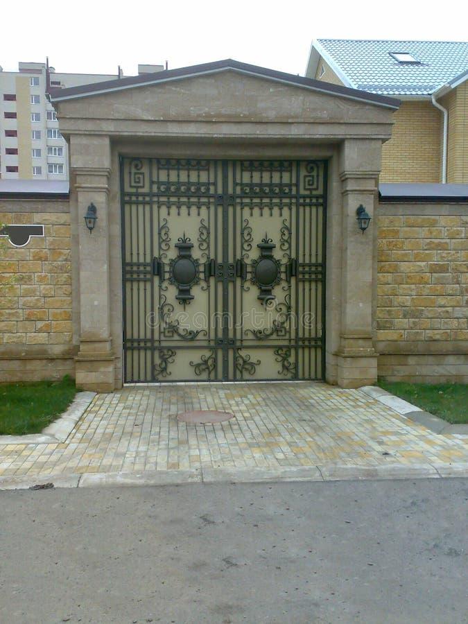 Beautiful gate. The gate is beautiful iron hammerwork brick masonry fence royalty free stock image